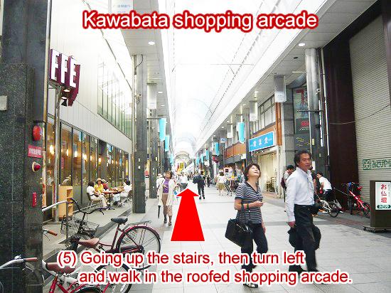 階段を上り、外に出て左折し、ショッピングアーケード内を進みます