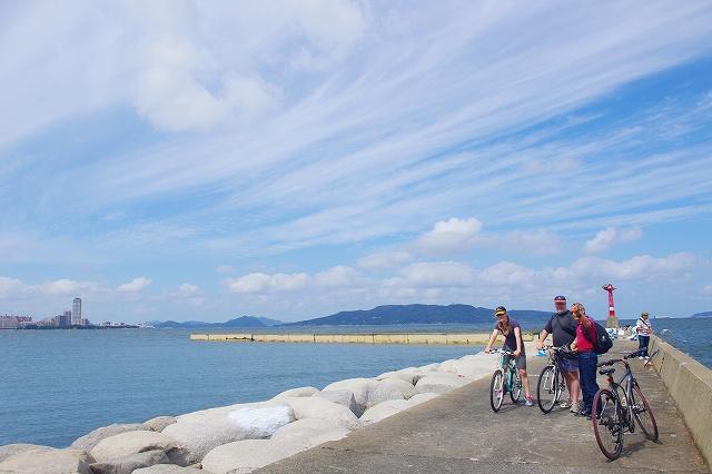 福岡バイクツアーページの海岸線を自転車で走る写真